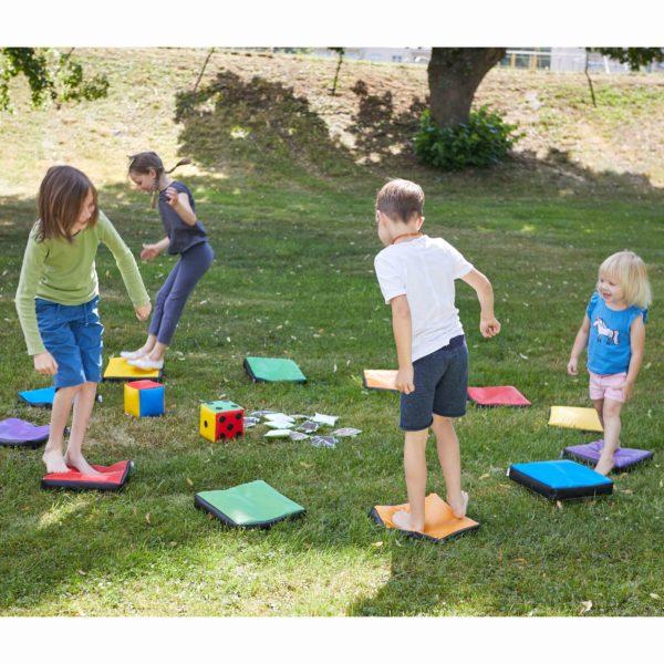 Kinder spielen mit Wahrnehmungskissen im Garten