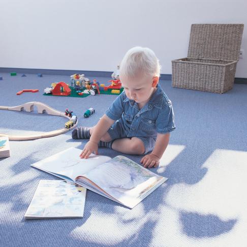 Kindergartenkind auf Spielteppich der Marke Mellon