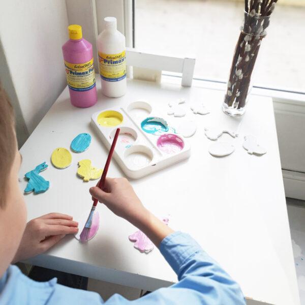 Kind malt Osteranhänger aus Modelliermasse an