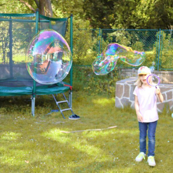 Kind macht Riesenseifenblasen