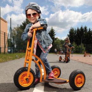 Kind im Kindergartenalter steht in cooler Pose mit Sonnenbrille auf dem robusten und sicheren Einstiegsroller Bengy von beleduc in orange