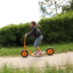 Kind im Vorschulalter braust auf dem robusten und sicheren Roller Scooter groß von beleduc durch den Garten