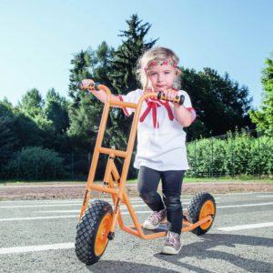 Mädchen im Kindergartenalter steht auf dem robusten und sicheren Roller Scooter klein von beleduc in orange
