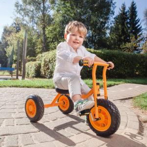 Bub im Krippenalter sitzt auf dem kleinen Dreirad von beleduc, das mit der geringen Sitzhöhe speziell für junge Kinder ab 2 Jahren geeignet ist und mit dem man ideal das Treten von Pedalen erlernen kann.