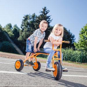 Mädchen im Kindergartenalter sitzt auf der bequemen, weil langen Sitzfläche des Dreirads Rookie während ein gleichaltriger Bub auf der stabilen Hinterachse steht.