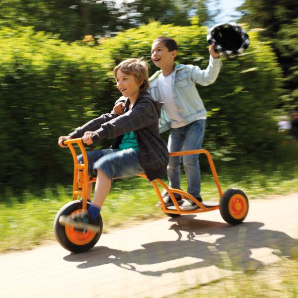 Zwei Buben im Volksschulalter sausen mit dem Dreirad Express durch den Garten - einer auf dem bequemen Sitz als Fahrer, einer auf dem Mitfahrstand mit Antirutschbrett und Brüstung