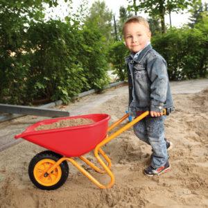 Bub im Kindergartenalter schiebt die leichte und robuste Scheibtruhe mit Sand beladen durch die Sandkiste