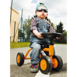 Kleiner Bub im Krippenalter sitzt in cooler Pose mit Sonnenbrille auf dem Laufrad Quaddy, das durch die vier robusten Räder für sichere erste Fahrversuche sorgt