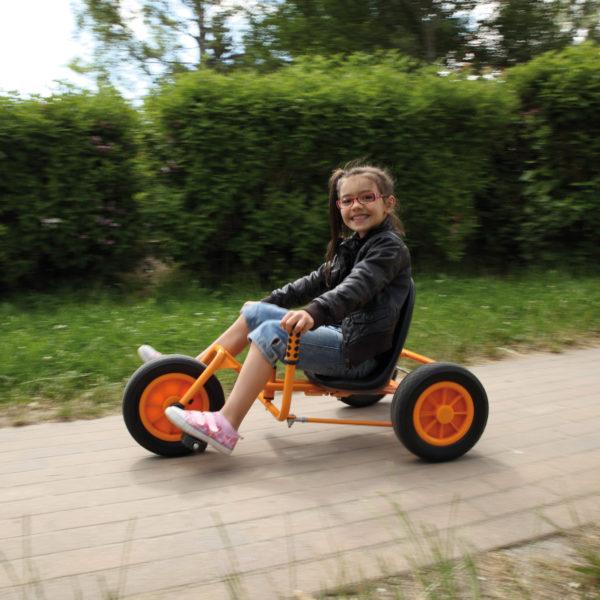 Kind im Volksschulalter saust mit dem Dreirad Rider, das über einen niedrigen Sitz und eine beidseitige Lenkvorrichtung in Höhe des Sitzes verfügt, durch den Garten.
