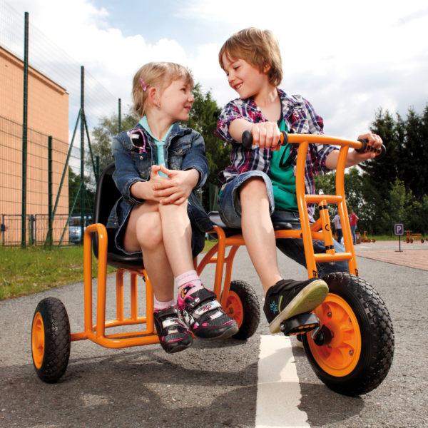 Zwei Kinder im Kindergartenalter sitzen Seite an Seite auf dem Dreirad Seitenwagen von beleduc