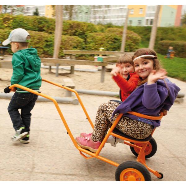 Zwei Kinder werden von einem Kind in der robusten Rikscha von beleduc durch den Garten gezogen