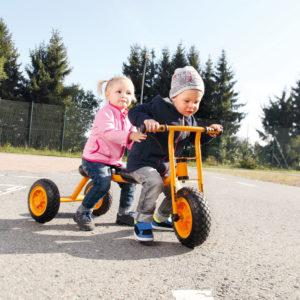 Zwei Kinder im Kindergartenalter fahren gemeinsam mit dem Laufrad Tandem wodurch die Koordination und das soziale Miteinander geschult werden.