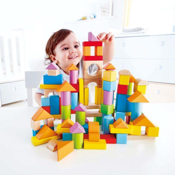 Kind spielt mit Holzbausteinen von Hape