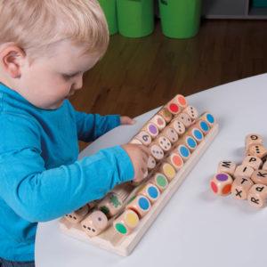 Kind spielt mit verschiedenen Würfel auf Würfelplatte von olifu