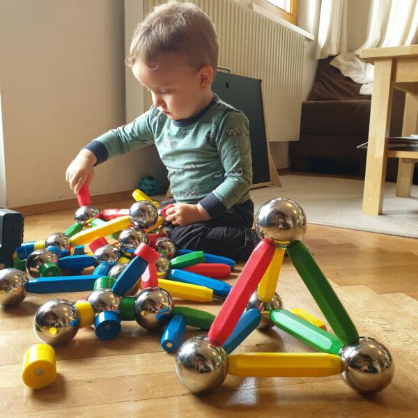 Kleinkind erforscht Magnetismus mit Kugeln und Stäben des Magnetspiels Maegie XXL