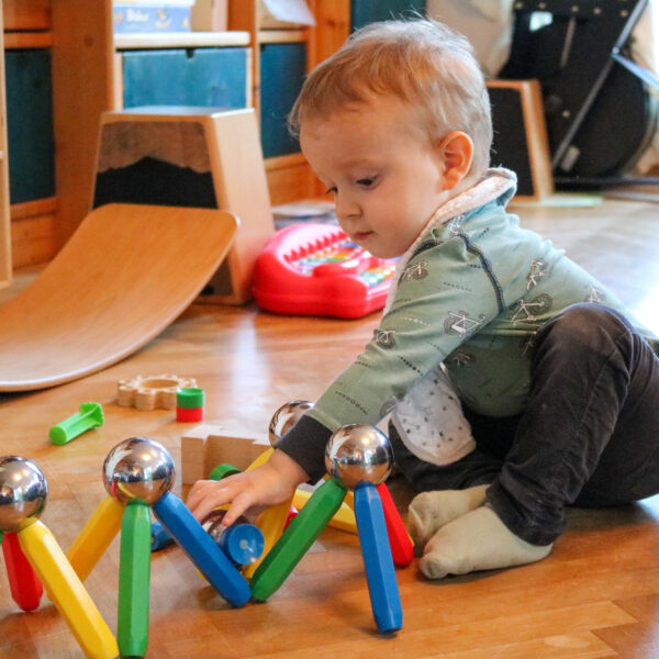 Kleinkind spielt mit bunten Stäben und Spiegelkugeln des Magnetspiels Maegie XXL