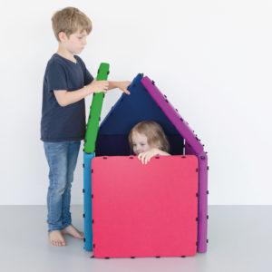 Bub im Vorschulalter baut kleines Häuschen aus Tuklus um Mädchen im Kindergartenalter