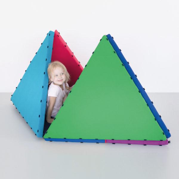 Mädchen im Kindergartenalter schaut aus einer selbstgebauten Höhle aus bunten Tukluk Schaumstoffbausteinen