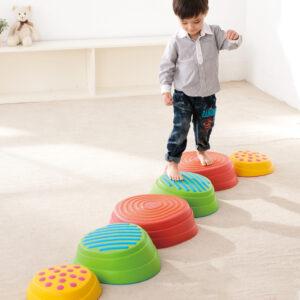 Kind geht über die Flussteine