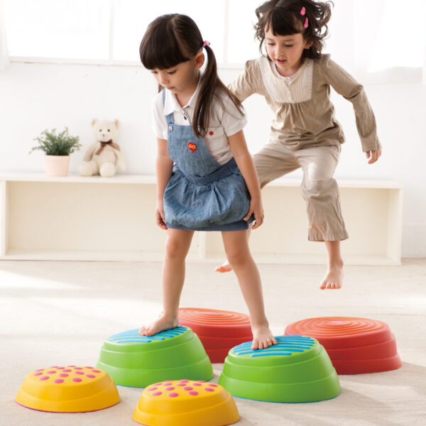 Kinder hüpfen auf die Regenbogen Flusssteine