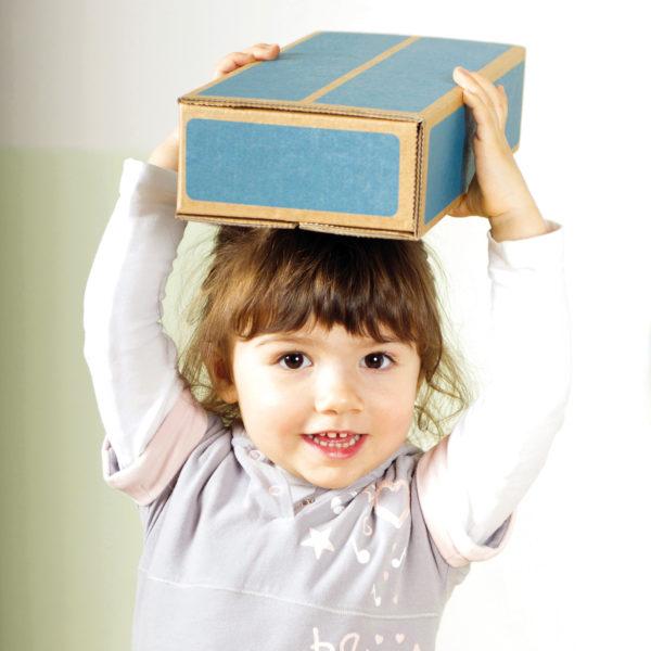 Mädchen im Kindergartenalter hält einen der federleichten und gleichzeitig robusten Kartonbausteine über dem Kopf