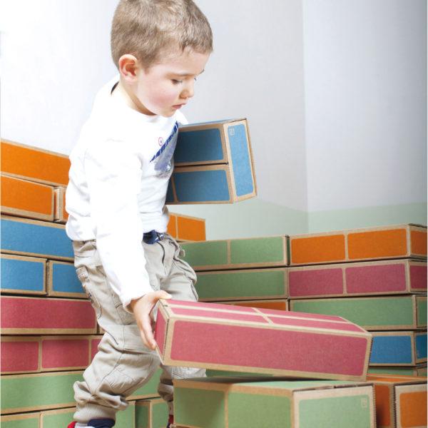 Bub im Kindergartenalter baut mit den federleichten und gleichzeitig robusten Kartonbausteinen in bunter Backsteinoptik