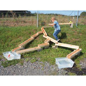 Kind spielt mit Wasserbahn aus Holz