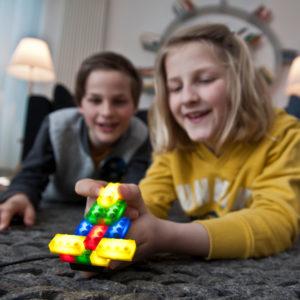 Zwei Buben im Volksschulalter spielen mit den leuchtenden, Lego® kompatibelen Leuchtbausteinen