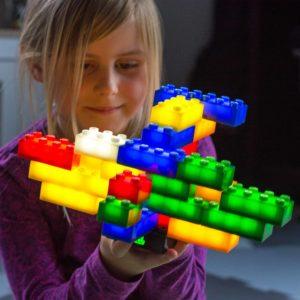 Kind im Kindergartenalter spielt mit den leuchtenden, Duplo® kompatibelen Leuchtbausteinen