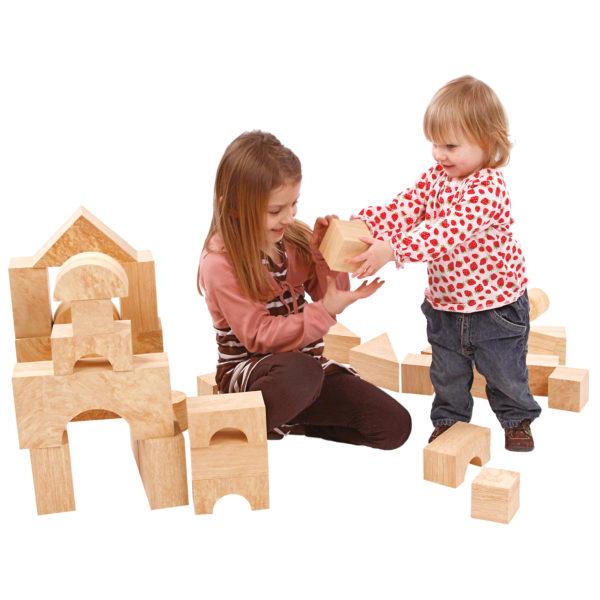 Mädchen im Kindergartenalter und Kind im Kleinkindalter spielen mit den weichen großen Softbausteinen in Holzoptik