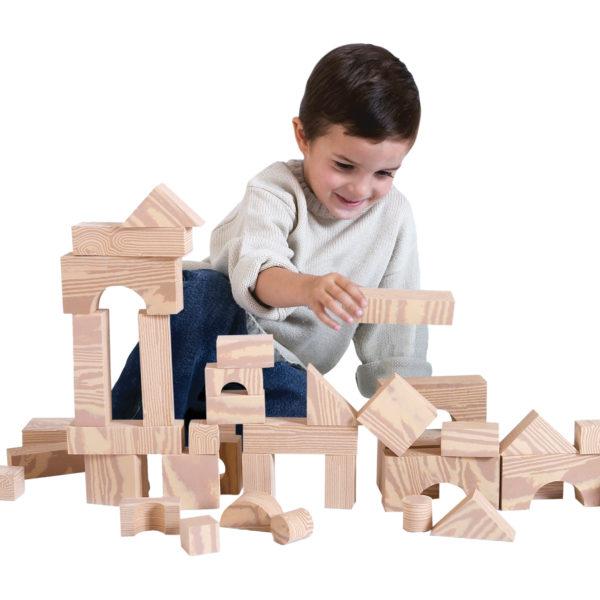 Bub im Kindergartenalter spielt mit den weichen kleinen Softbausteinen in Holzoptik