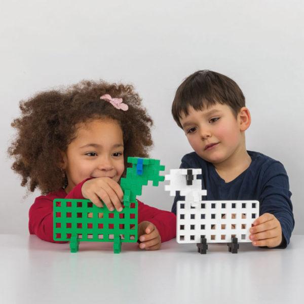 Kinder spielen mit Tieren aus Plus Plus Bausteinen
