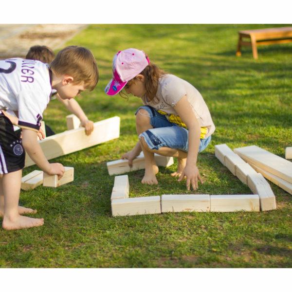 Kinder bauen Mauer mit den Bausteinen des Kreativ Holz Wunderbaum