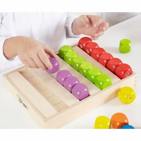 Kind legt bunte Fädelwürfel in die Würfelbox von olifu
