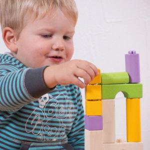 Kind im Kindergartenalter spielt mit den Holzbausteinen von Olifu