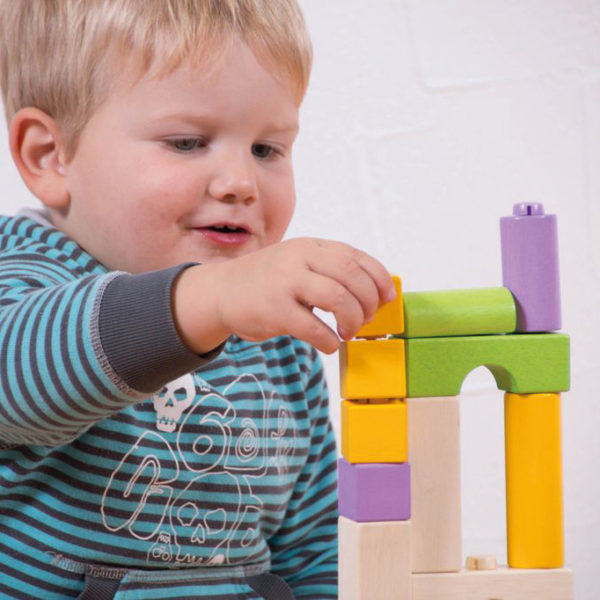 Kind im Krippenalter spielt mit den Holzbausteinen von Olifu