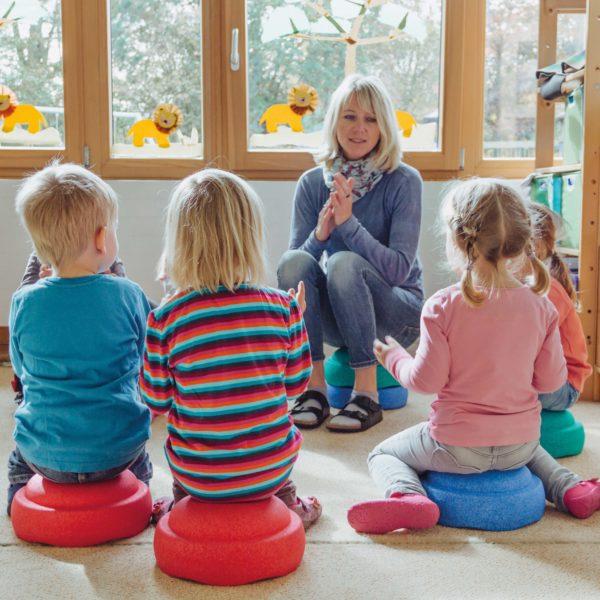 Kinder sitzen auf Stapelsteinen im Kreis