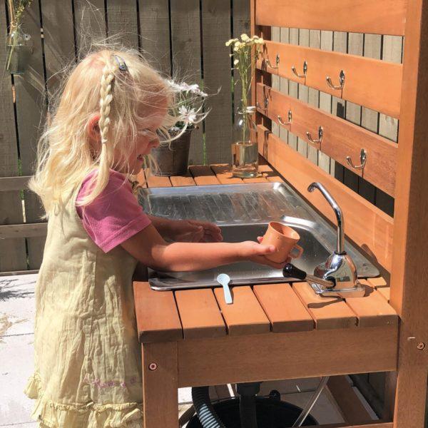 Kind spielt mit der Outdoor Küche mit Wasserpumpe