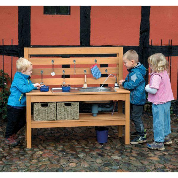 Kinder spielen mit Outdoor Matschküche mit Wasserpumpe