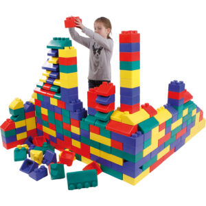 Kind im Kindergartenalter baut mit den stabilen und leichten Softbausteinen ohne große Kraftanstrengung eine riesige Burg um sich