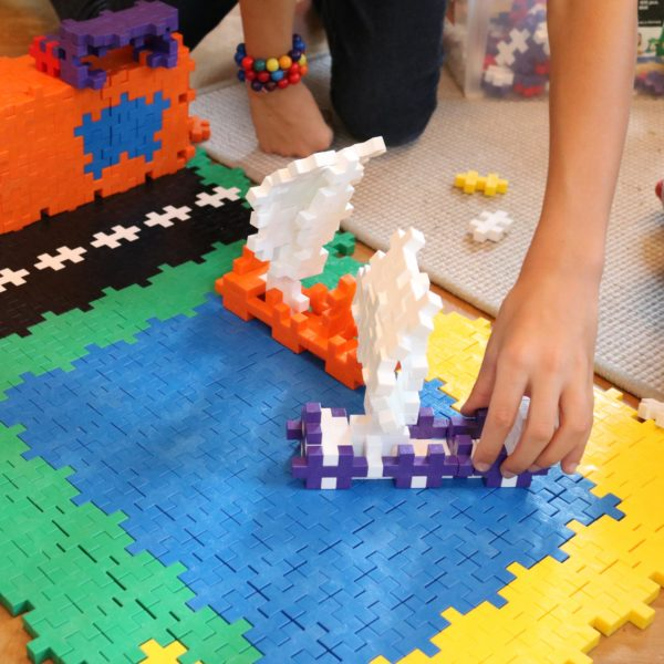 Kind spielt mit kleiner Welt gebaut aus Plus Plus Bausteinen