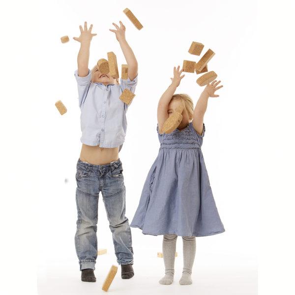 Kinder werfen Korkbausteine in die Luft