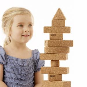 Kind baut mit Turm aus Korkbausteinen von KORXX