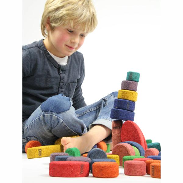 Kind spielt mit Bausteinen aus buntem Kork von KORXX