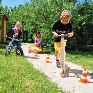 Kinder fahren einen Parcour mit Markierungskegeln