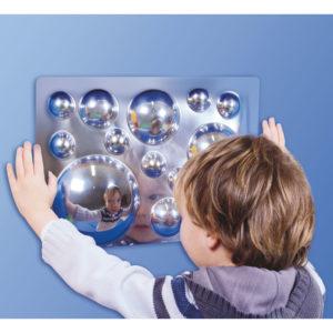 Kind schaut sich in den Acrylspiegel