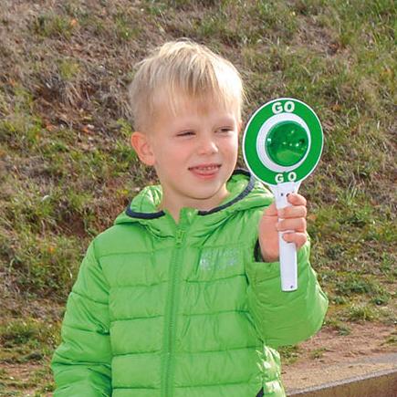Kind hält Spielzeug-Polzeikelle mit grünem und rotem Licht