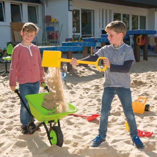 Kinder spielen mit Scheibtruhe im Sand