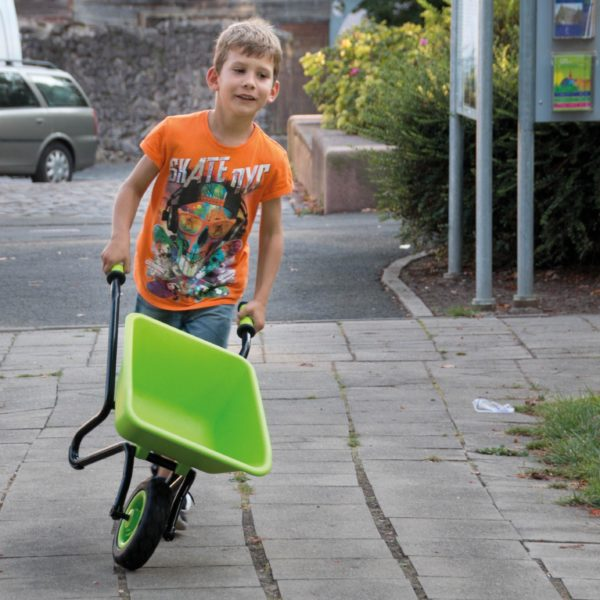 Kind fährt mit Scheibtruhe