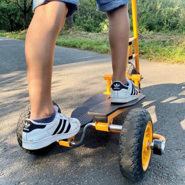 Kind macht Trittbewegungen auf Toptrike Step'n Roll Fahrzeug
